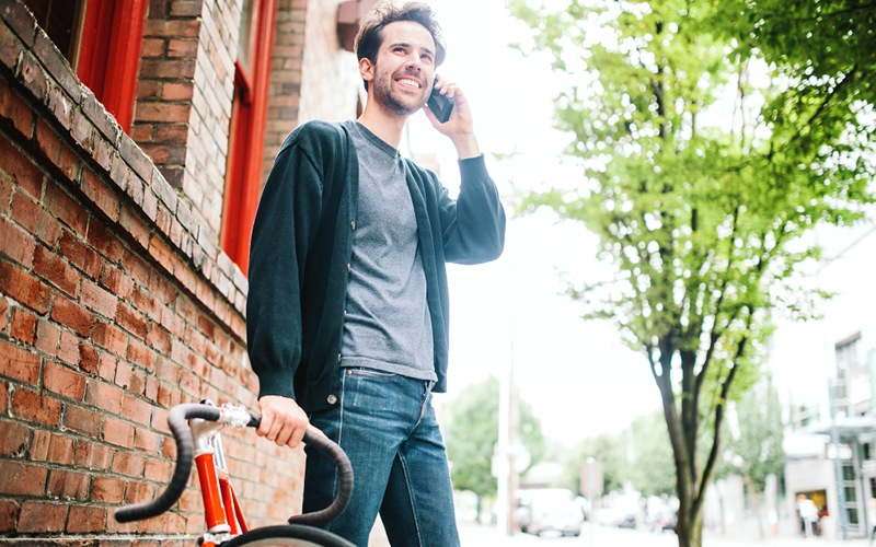 Man standing by bike on phone.